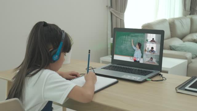 vídeos de stock, filmes e b-roll de estudante asiática vídeo-conferência e-learning com professor e colegas de classe no computador na sala de estar em casa. homeschooling e ensino a distância, online, educação e internet. - salas de aula