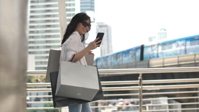 vídeos y material grabado en eventos de stock de chica asiática navegando por la red con smartphone para ir de compras - shopping bags