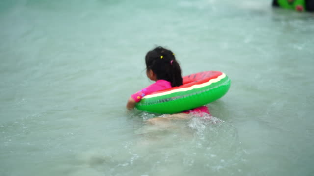 asian girl swimming in sea with buoy