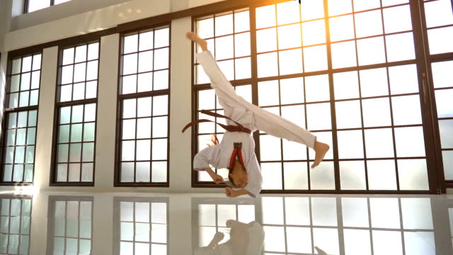Asian girl taekwondo jumping somersault