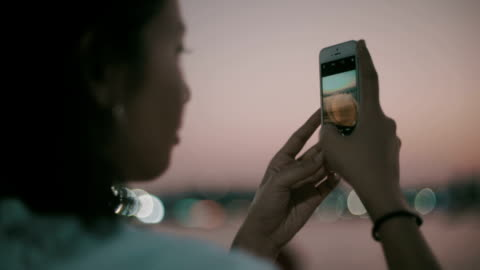 Asian girl take a photo Closeup of asian young tourist woman photographs ocean view with smartphone during sunset at beach ,lifestyle concept advertisement stock videos & royalty-free footage