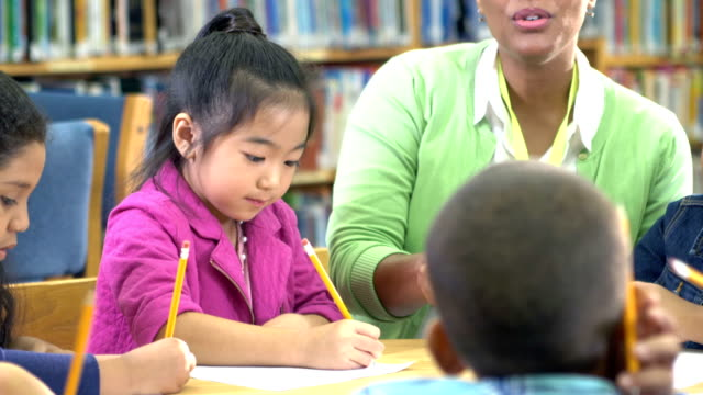 Asian girl, teacher, classmates writing in library video