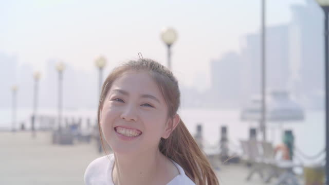 stockvideo's en b-roll-footage met slo mo aziatisch meisje zich afwenden en springen met glimlach - oost azië