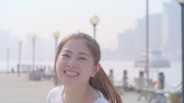 vídeos de stock, filmes e b-roll de menina asiática de slo mo voltar e saltar com sorriso - só mulheres