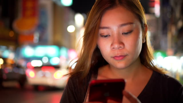Asian Girl using Mobile Phone During Walk on Streets of Night Town video