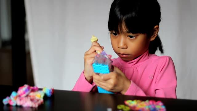 Asian Girl Using Rainbow Loom video
