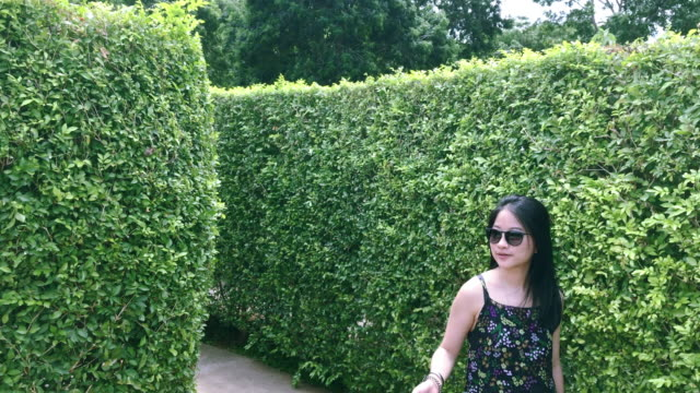 Asian girl walking in maze garden at noon. Asian girl walking in maze garden at noon. midday stock videos & royalty-free footage