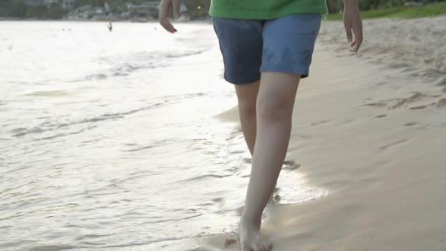 asian girl walking leisurely on the beach with waves washed up on the coast. - pantaloncini video stock e b–roll
