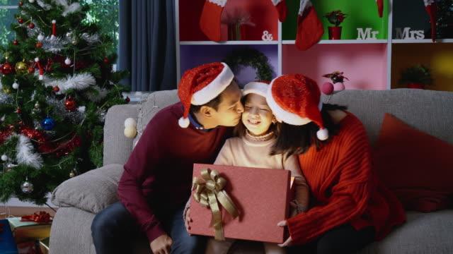 ms, asiatische mädchen mit familie eröffnung eines weihnachtsgeschenks. - weihnachtsstrumpf stock-videos und b-roll-filmmaterial