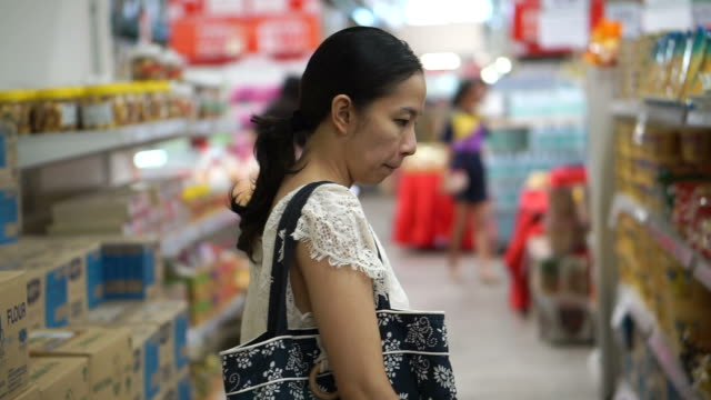 Asian girl, woman shopping for food in wholesale supermarket video