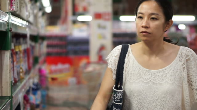Asian girl, woman walking, looking and shopping snacks in supermarket isle video