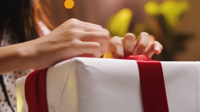 Asian girl wrapping gift box with red ribbon in Christmas Day.