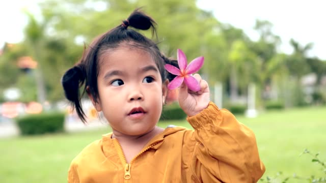 Asian girl-child show pink flower and spinning