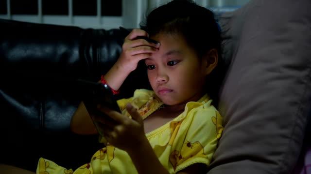 asiatiska tjejer spelar mobiltelefon - ligga på mage bildbanksvideor och videomaterial från bakom kulisserna