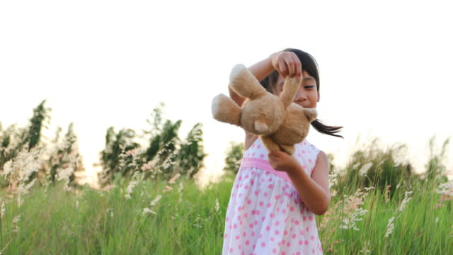 Asian Girls playing teddy bears and laughing happy on meadow in summer in nature