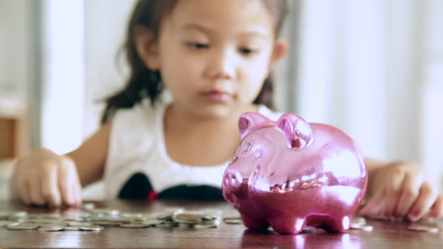 Asian girls with savings for the future Cute girl putting coins into piggy bank at home piggy bank stock videos & royalty-free footage