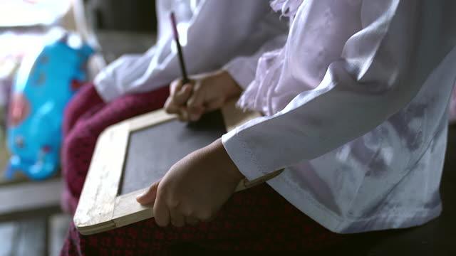 asyalı kızlar bir kara tahta alfabesi yazma ve arduvaz kurulu üzerinde yazma çocuklar gösteren. yoksulluk çocuklar alfabe öğrenmek için arduvaz kara tahta kullanarak. - el aleti stok videoları ve detay görüntü çekimi
