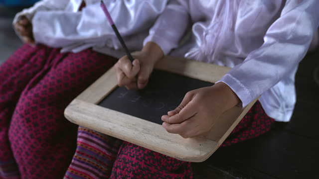Asian girls writing the alphabet in a chalkboard and showing children writing on slate board.Poverty children using the slate chalkboard to learning alphabet.