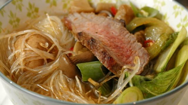 vídeos y material grabado en eventos de stock de sopa de fideos asiáticos de vidrio con la carne de vacuno y pak choi - pak choy