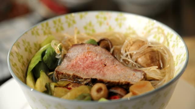 Sopa de fideos asiáticos de vidrio con la carne de vacuno y Pak Choi - vídeo