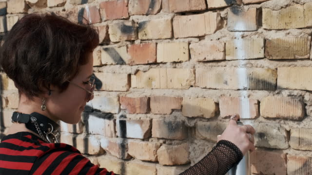 Asian gothic teenager girl draws a spray paint spray on wall line on old brick wall of an abandoned building, slow motion. Protest. Alternative in youth. Hipster, freak, emo, grunge, punk. Copy space