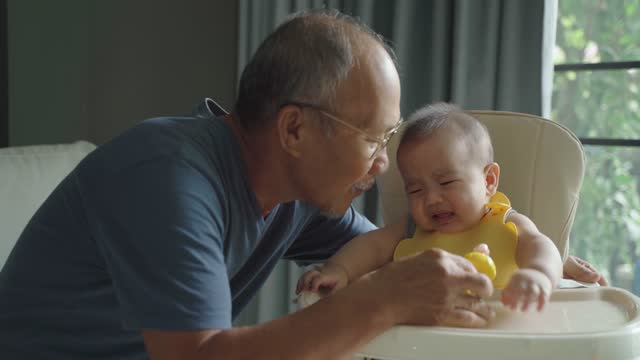 Asian Grandfather consoling his little baby in a feeding chair while meal at home