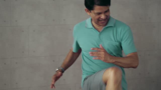 asian grandfather exercises at home. - chudy filmów i materiałów b-roll