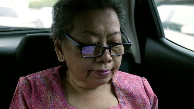 アジアのおばあちゃんと車にデジタル タブレット - 乗客点の映像素材/bロール