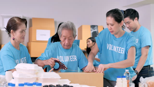 아시아 할머니 는 70 세의 자원 봉사자가 상자 무료 음식 배달을 포장하고 그룹 친구가 위기 코로나 바이러스 covid-19에서 사람들을 위해 옷을 포장합니다. 자원 봉사 - giving tuesday 스톡 비디오 및 b-롤 화면