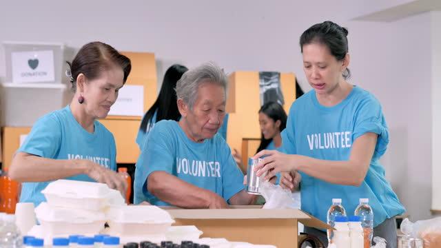아시아 할머니 는 70 세의 자원 봉사자가 무료 음식 배달을 준비하는 동안 그룹 친구가 위기 코로나바이러스 covid-19에서 사람들을 위해 옷을 포장합니다. 자원 봉사 - giving tuesday 스톡 비디오 및 b-롤 화면
