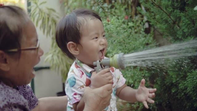 Grand-mère asiatique et enfants arroser un arbre ensemble à la maison. - Vidéo