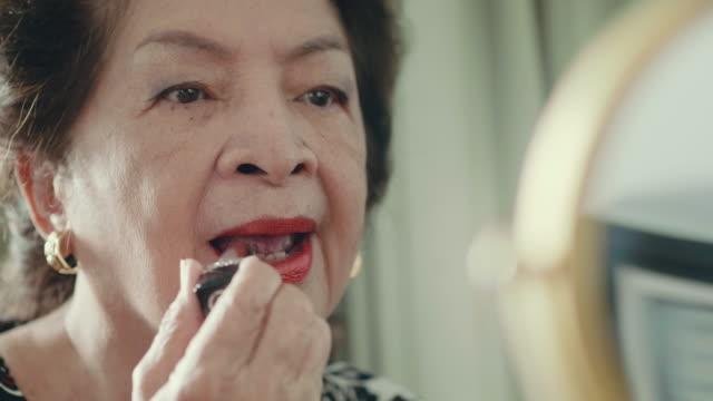 asiatische großmutter anwendung make-up - lippenstift stock-videos und b-roll-filmmaterial