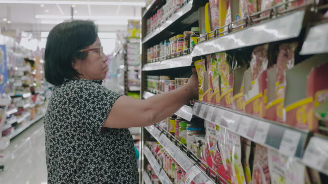 vídeos y material grabado en eventos de stock de abuela asiática en tienda de abarrotes - eventos de etiqueta