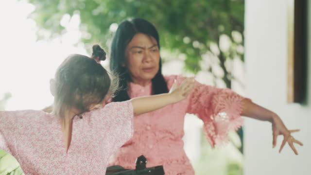 vídeos y material grabado en eventos de stock de abuela asiática es vuelo e imitación de pájaro mientras su nieta con la emoción positiva de la enseñanza - copiar