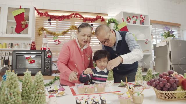 asiatiska morförälder och liten pojke gör kakor och bageri vid jul - pepparkaka bildbanksvideor och videomaterial från bakom kulisserna