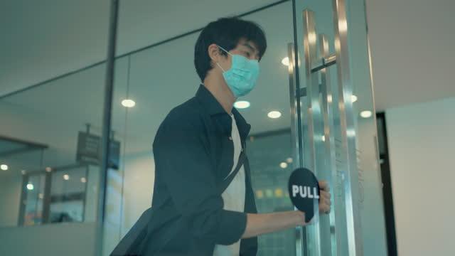 Asian graphic designer wear surgical mask entering to design studio.