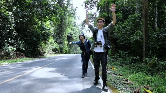 Asian Group tourists and backpackers catches the car and Freedom traveler standing with raised arms at the roadside.