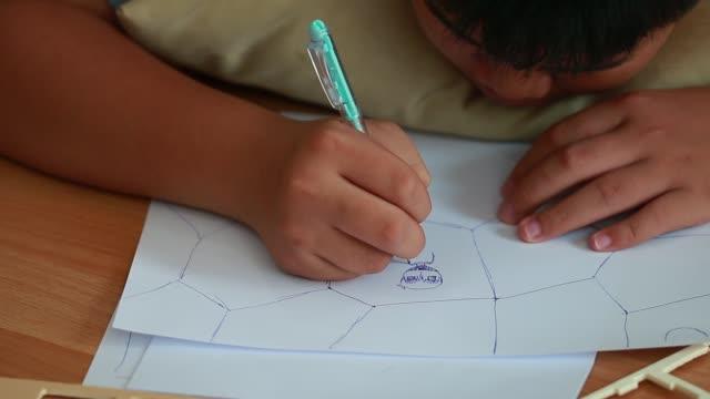 小学生の私立教室で紙のレイアウトで創造的なストーリーテリングのための絵本漫画のキャラクターを描くアジアの手の子供の学生。教育学習コンセプトでくつろぐ趣味 - スケッチ点の映像素材/bロール