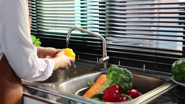 Asian hands woman washing fruit orange and preparation healthy food in kitchen.