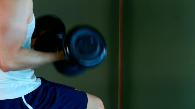 asiatische gut aussehender mann spielt hantel auf heim-fitness-lifestyle - hantel stock-videos und b-roll-filmmaterial