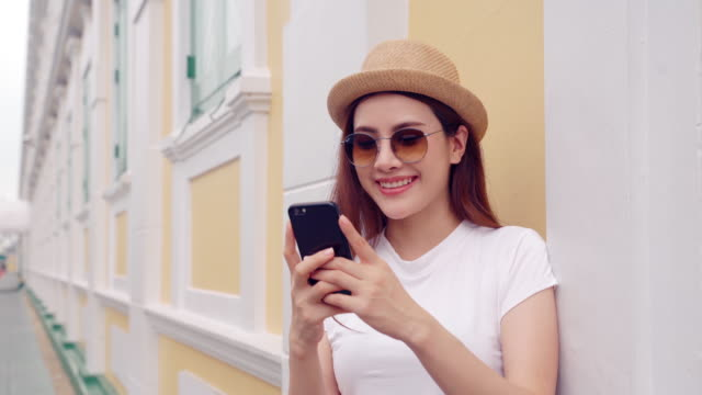 Asian Handsome young business woman using smart phone smiling happy wearing shirt ,sms texting woman using phone in Bangkok city, people of all ages connecting with each other through technology ,Happiness Means Everything as inspiration concepts,