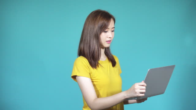 Asian happy beautiful cute young woman teen her holding laptop computer and excited celebrating after check email, looking to the camera in studio, isolated on blue background, 4k video solution