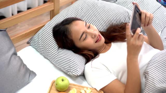 アジアの幸せな女の子寝室のスマート フォンを使用して、ドーナツ、フルーツ、コーヒーを飲み - スマホ ベッド点の映像素材/bロール