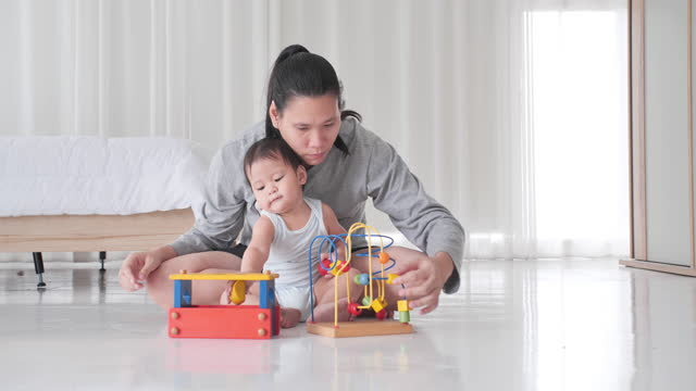 Asian happy mother teach little boy son age 10 month playing with wooden blocks on floor, cute small child having fun building tower of colorful wooden blocks at home.South East and East Asia: Asian Babies video