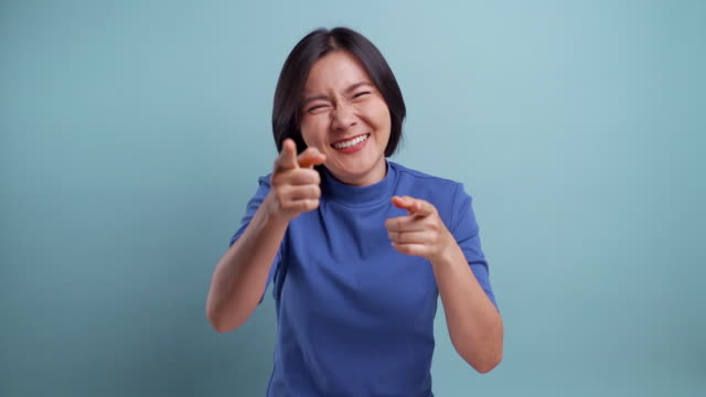 Asian happy woman looking at camera and pointing to camera, i want you concept. isolated on blue background slow motion video