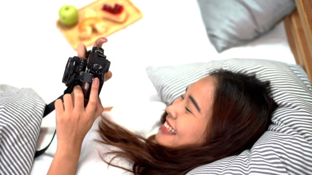 Asian happy women looking a photo camera on bedroom and drinking cup of coffee with donuts and fruit