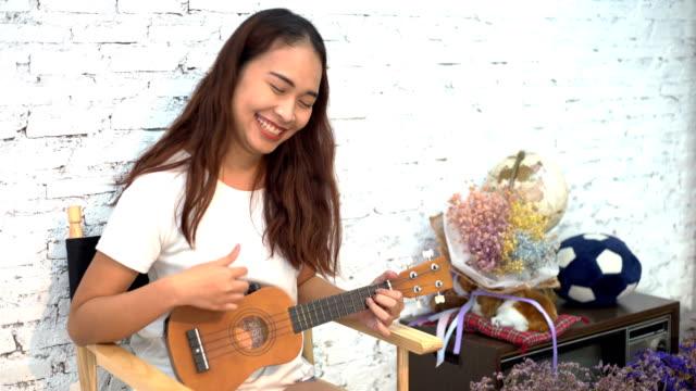 asiatiska glada kvinnor som spelar akustisk gitarr med vit bakgrund - akustisk gitarr bildbanksvideor och videomaterial från bakom kulisserna
