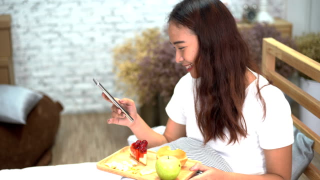 Asian happy women  using smart phone on bedroom and drinking cup of coffee with donuts and fruit