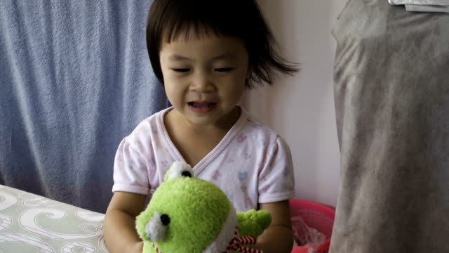Asian Happy Young Girl With Green Frog Doll video