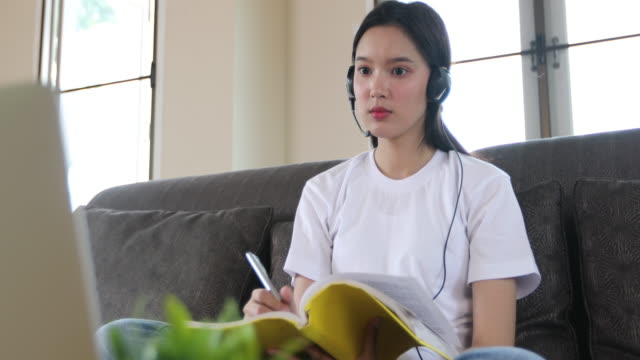 Asian happy young woman student wear headphones study online watching webinar podcast on laptop listening learning education course conference calling and write notes look at laptop sitting on the sofa at home, e-learning and homeschool concept video